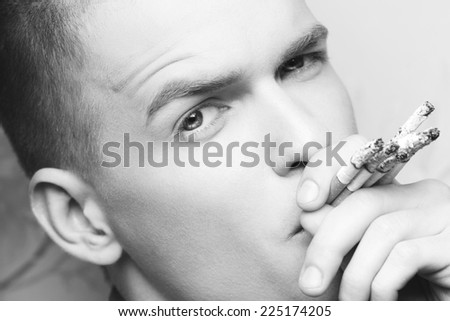 Stop Smoking Concept. Emotive portrait of young fashionable model smoking too many cigarettes. Retro style. Close up. Black and white studio shot - stock photo
