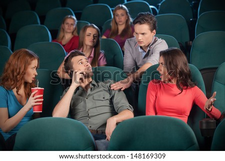 Stop talking! Young men talking at phone while watching movie at the cinema - stock photo