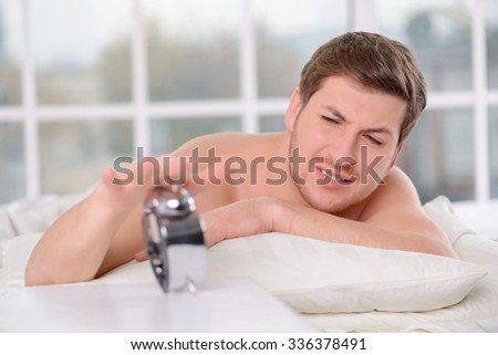 Stop the alarm. Handsome young man frowns irritated and reaches out to turn the alarm clock off. - stock photo