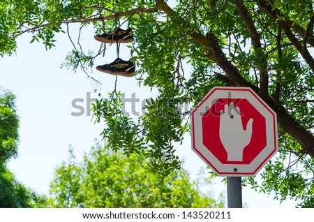 Stop traffic sign and sneakers on the tree near junction - stock photo