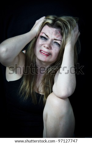 STOP Violence With Women, Scared white woman holding her head in pain with a black background - stock photo