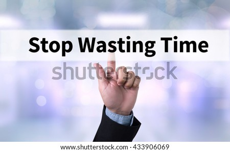 Stop Wasting Time Business man with hand pressing a button on blurred abstract background - stock photo