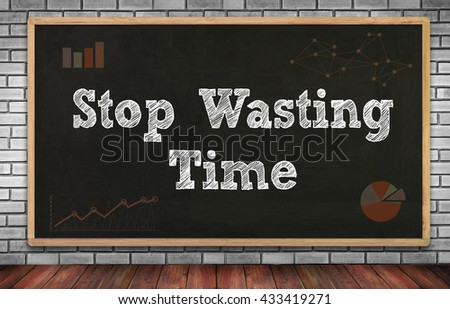 Stop Wasting Time on brick wall and chalkboard background - stock photo