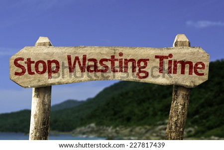 Stop Wasting Time wooden sign with a beach on background - stock photo