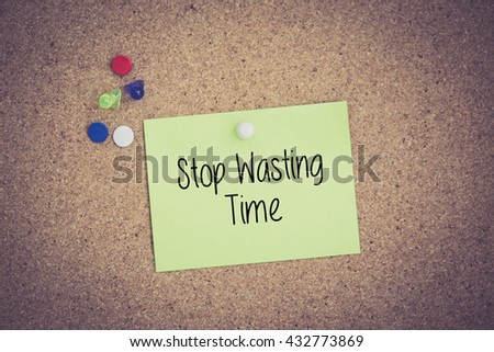 Stop Wasting Time written on sticky note pinned on pinboard - stock photo