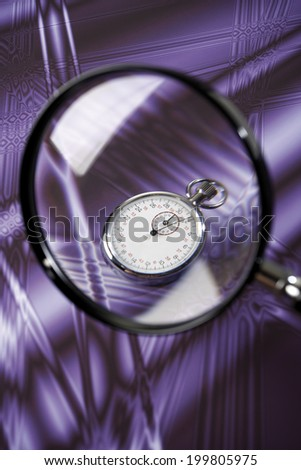 Stop watch under magnifying glass - stock photo