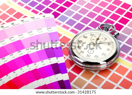 Stopwatch and a color guide on printed color chart (purple pink and red) - stock photo