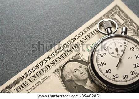 Stopwatch and dollars on a grey background - stock photo
