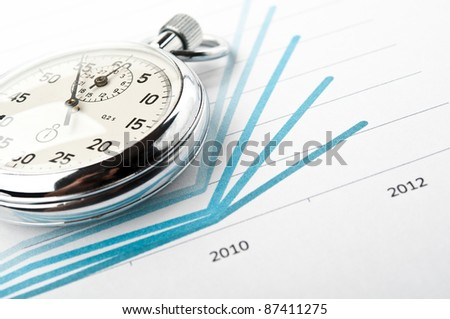 stopwatch and financial growth chart on the table in the office - stock photo