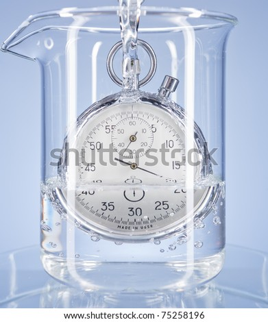 Stopwatch in a glass with water on a blue background. Metaphor of flowing away time. - stock photo