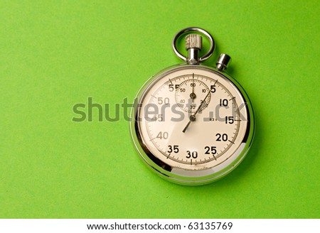 Stopwatch isolated on green background - stock photo