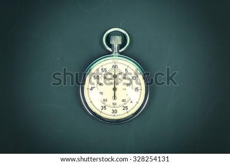 Stopwatch On blackboard - stock photo