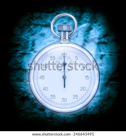 Stopwatch on cracked wall background in blue toning - stock photo