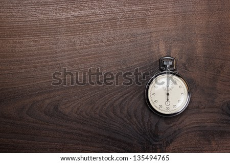 stopwatch on the brown wooden table background - stock photo