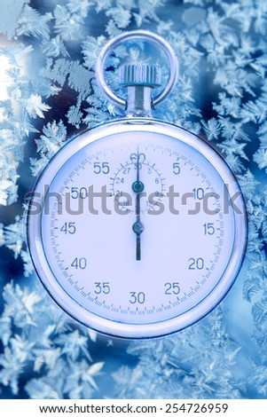 Stopwatch on winter window ice frozen background  - stock photo