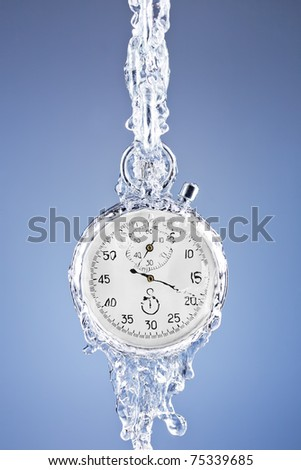 Stopwatch surrounded by a stream of water on a blue background. Metaphor of flowing away time. - stock photo