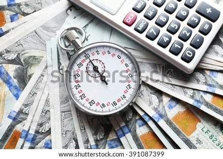 Stopwatch with calculator on dollar banknotes. Time is concept - stock photo