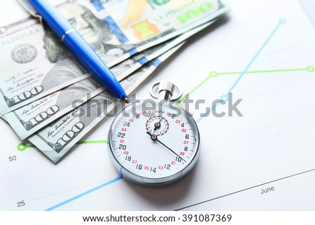 Stopwatch with dollar banknotes and pen on paper background - stock photo