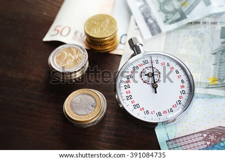 Stopwatch with euro banknotes and coins on wooden background. Time is money concept - stock photo