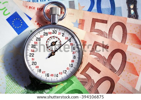 Stopwatch with euro banknotes on blue background. Time is money concept - stock photo