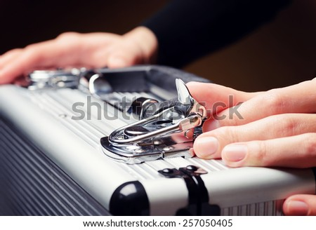 Storage and protection of cash and valuable goods. Business man opens an aluminum briefcase. Money and documents in safe hands of bank employee. - stock photo