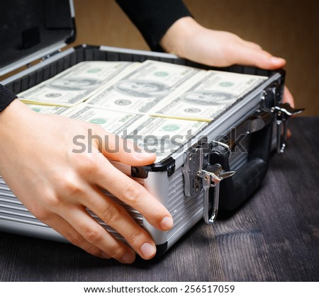 Storage and protection of cash and valuable items. Banking concept. Business man opens an aluminum briefcase full of stacks of hundred-dollar bills before a deal. Money in safe hands. - stock photo