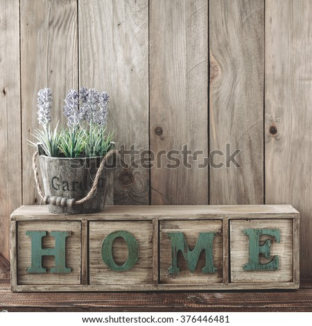 Storage box with Home letters and flowers in a pot on wooden background, home rustic decor, cottage living - stock photo