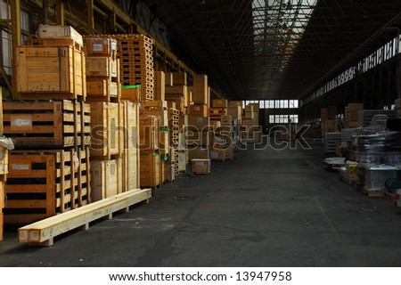 Storage hall with wooden crates packed with industry items.