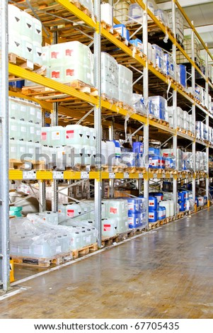 Storage rack in warehouse with chemical liquids - stock photo
