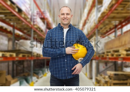 storage, shipment, logistic business, people and export concept - happy man with hardhat over warehouse background - stock photo