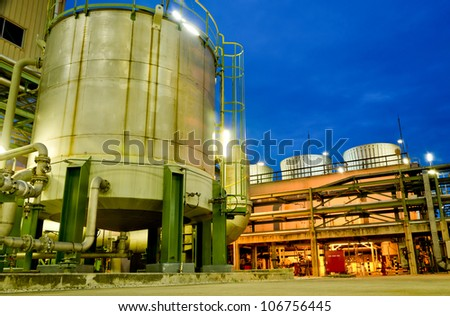 Storage tank and cooling tower in petrochemical plant - stock photo