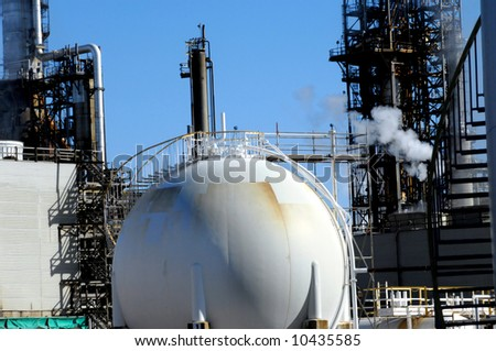 Storage tank is round and white with ladder running up side.  Industrial scene in background complete with steam and stack.