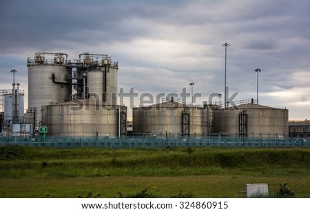storage tank ,over dark clouds - stock photo