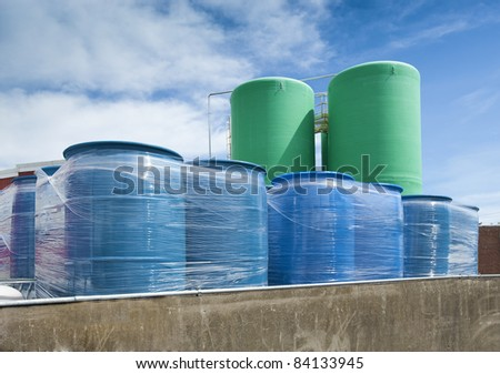 Storage tanks and blue chemical plastic drums - stock photo