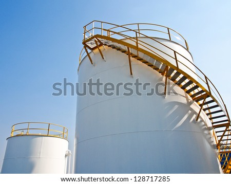 storage tanks in oil refinery plant with blue sky - stock photo