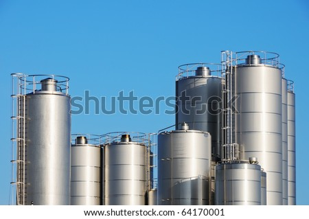 Storage tanks of dairy plant against blue sky. - stock photo