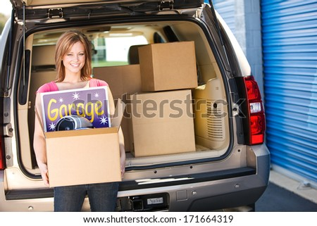 Storage: Woman Carrying Leftovers From Garage Sale - stock photo