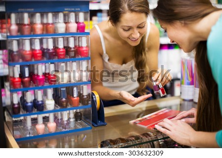 Store clerk serving purchaser with nail polish in the shopping mall