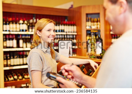 Store manager and saleswoman doing inventory with mobile data registration terminal - stock photo