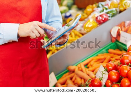 Store manager doing warehouse management with tablet computer in a supermarket - stock photo