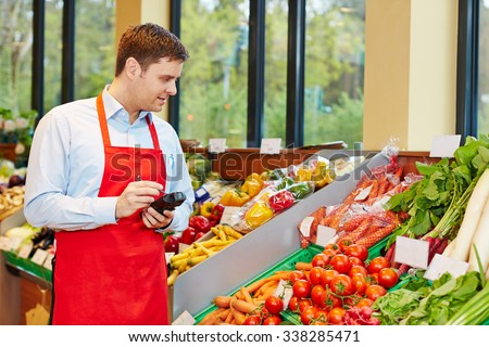 Store manager in supermarket ordering fresh vegetables with mobile data registration terminal