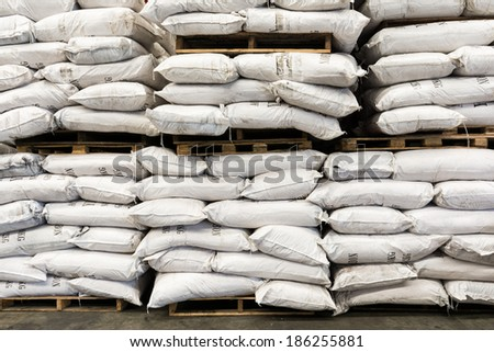 storehouse with stacked dirty sacks of chemical product - stock photo