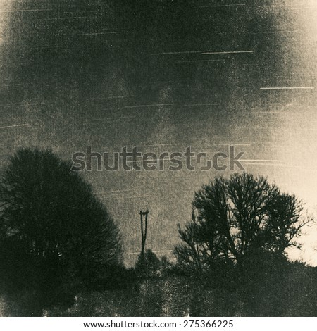 Stork nest pole surrounded by trees at night, vintage grunge picture, paper background with leaks, grain and noise - stock photo