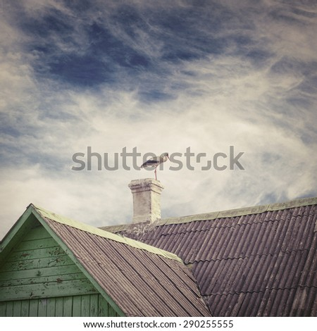 Stork standing on a chimney of old house with a tiled roof, dramatic blue sky background - stock photo