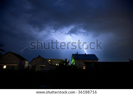Storm and lighting over house. Thunderstorm at night near village. - stock photo
