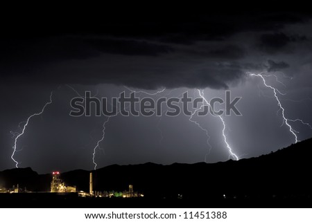 Storm and lightning advance on an industrial plant