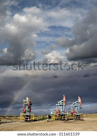 Storm and rainbow over oil pumps. Oil field. Gas industry. - stock photo