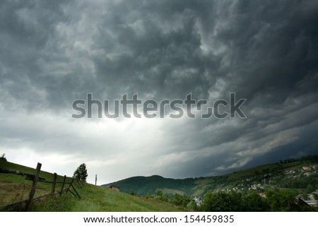 Storm clouds above a mountain village - stock photo