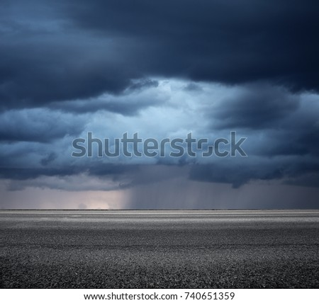 Storm clouds above asphalt road, side view. Landscape in rainy day