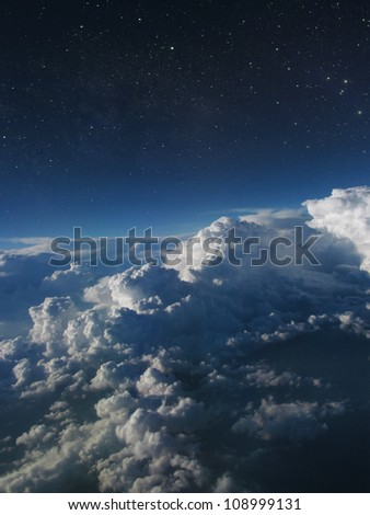 Storm clouds against a dark sky with stars.  Room for your text. - stock photo